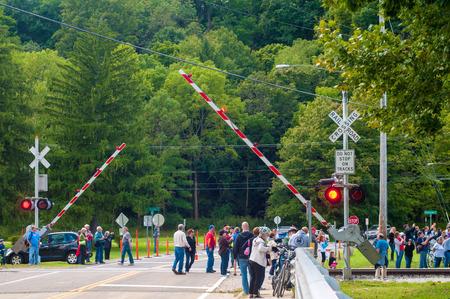 flashers: BRECKSVILLE, OH - 14 de septiembre 2014: Los espectadores aguardan la llegada de un tren de vapor en un paso a nivel en el Cuyahoga Valley Scenic Railroad, parte del vapor anual en el Valle.