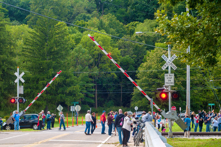 flashers: BRECKSVILLE, OH - SEPTEMBER 14 2014: Spectators await the approach of a steam train at a grade crossing at on the Cuyahoga Valley Scenic Railroad, part of the annual Steam in the Valley.