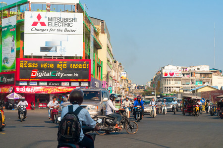 PHNOM PENH, CAMBODIA - FEBRUARY 27, 2014: A busy intersection in the Cambodian capital has traffic moving in many directions under signs of booming economic activity.