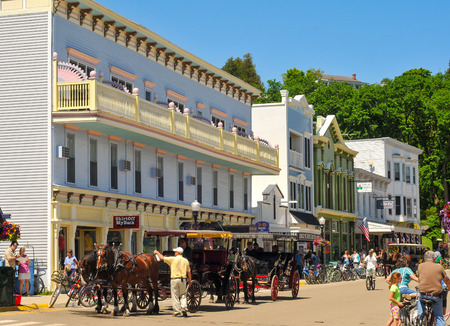 thronged: MACKINAC ISLAND, MI - JUNE 26, 2014: Main Street on Mackinac Island is thronged with tourists on a bright summer day and is the point of embarkation for many of the island carriage tours.