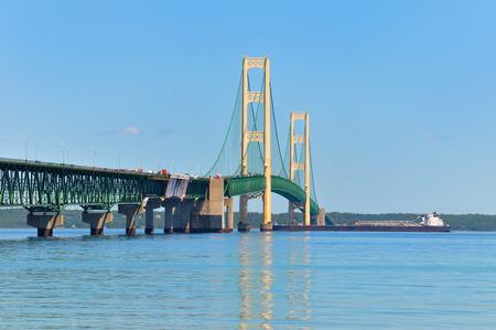 freighter: A lake freighter crossing under the Mackinac Bridge, heading from Lake Huron to Lake Michigan
