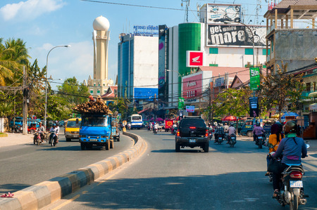 high rises: PHNOM PENH CAMBODIA  FEBRUARY 28 2014: Traffic makes its way along Preah Monivong Boulevard in the crowded Cambodian capital past modern high rises and thriving commerce.