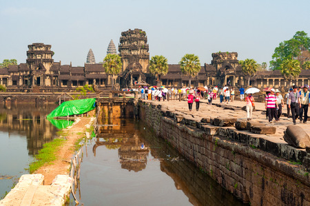 perimeter: SIEM REAP CAMBODIA  FEBRUARY 17 2014: Throngs of visitors cross the moat that surrounds the temple complex of Angkor Wat. Just past the causeway is the west perimeter gallery beyond which two towers of the main shrine can be seen. Editorial