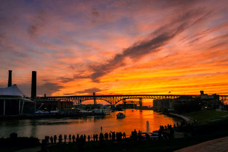 solstice: A silhouetted crowd of phototgraphers lines the east bank of the Cuyahoga River in Cleveland to shoot the summer solstice sunset