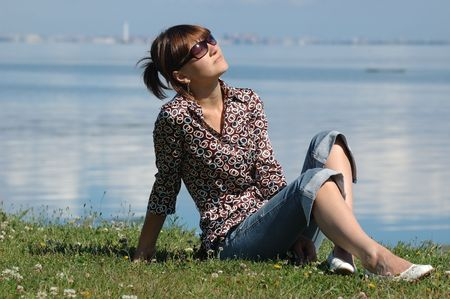 Girl sitting on grass and taking the sun. There are sea and the city in the background photo