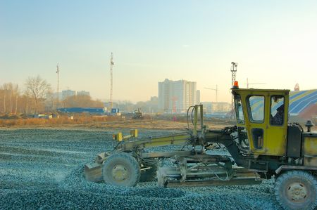 grader: Grader levels out crushed stone on the construction site