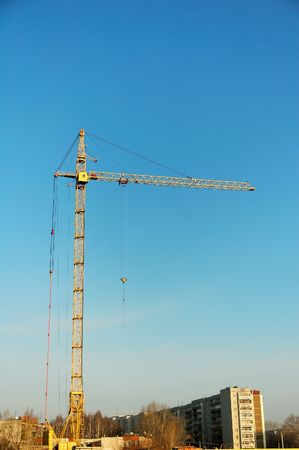Construction crane at building site at blue sky photo