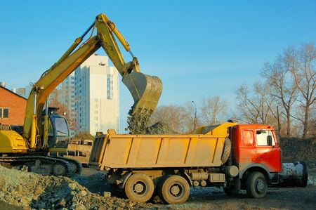 excavator and truck at building site Stock Photo