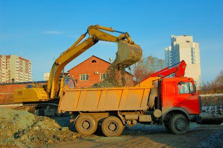 dumptruck: Building site. Excavator pours soil into the dump-truck Stock Photo