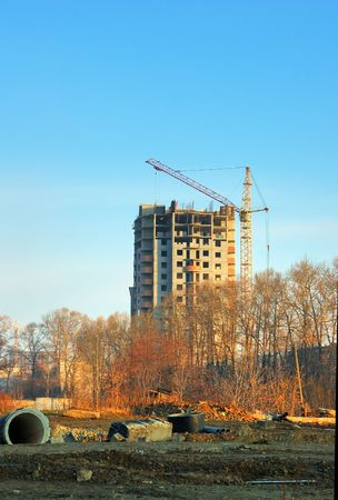 Construction crane and building site at blue sky (sunrise light) photo