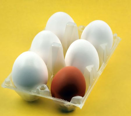 yelloow: One brown egg among of white eggs on yellow background Stock Photo