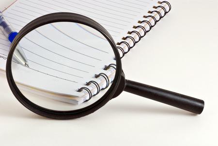 メモ帳とペンの上の拡大鏡のガラス