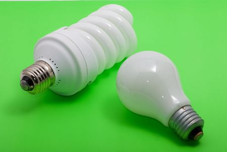 An energy efficient bulb and a ordinary electric bulb. Isolated on a green background photo