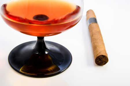 Snifter with brandy and havana cigar over white photo