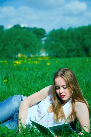 girl read a book on meadow photo