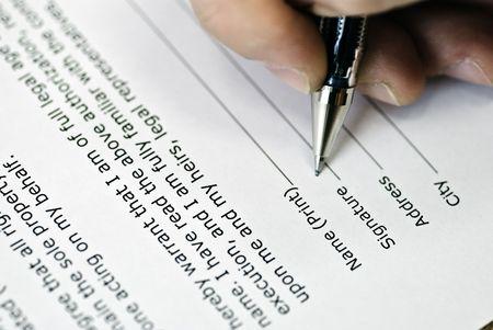 hand met een pen maakt de ondertekening van een akkoord