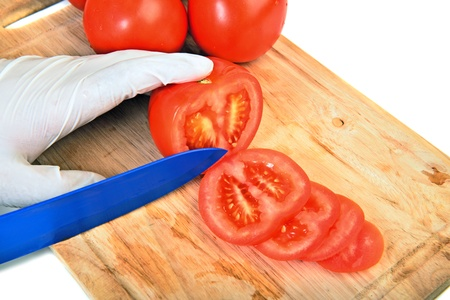 slicing: Slicing tomato on cutting board with ceramic knife over white Stock Photo
