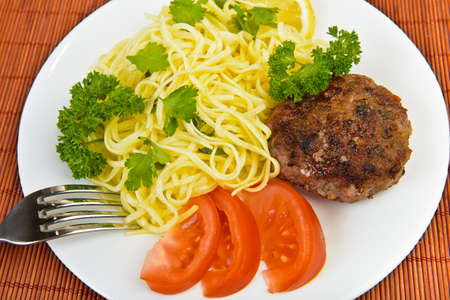 Burger rissole  and spaghetti with vegetables at plate photo