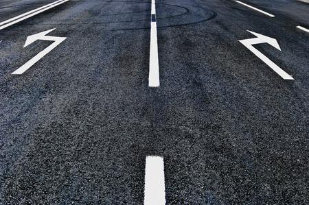 dividing: Arrow signs on asphalt road Stock Photo