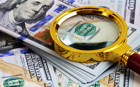 us paper currency: Investment analysis. Stack of US Dollar and magnifying glass Stock Photo