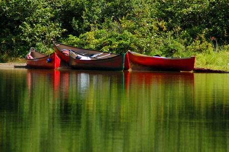 canoes: Colourful canoes around the portage Stock Photo