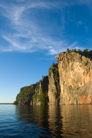 High cliff at shore of Mazinaw Lake in sunset light Stock Photo - 1630241