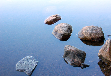 Six stones in blue lake water photo