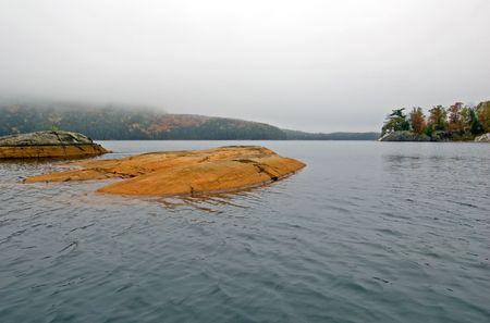 provincial: Small rock island in Killarney lake at overcast day Stock Photo