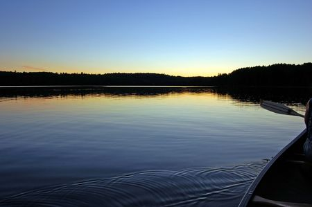 provincial: Sunset and canoe trip in calm lake in Algonquin Park