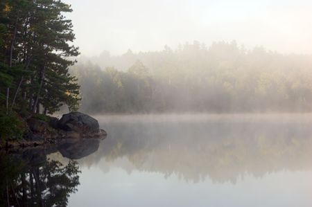 mirror on the water: Fog above forest lake in Killarney Park in the morning Stock Photo
