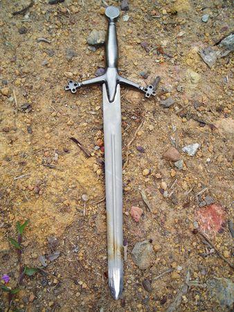 Sandy soil: espada en la suciedad de fondo de grava