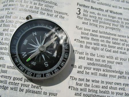 Una bussola e una bibbia sul verse di fiducia di proverbi 3:5-6 nel SIGNORE con tutto il vostro cuore e la magra non sulla vostra propria comprensione, in tutti i vostri sensi lo riconoscono e render� i vostri percorsi diritti.