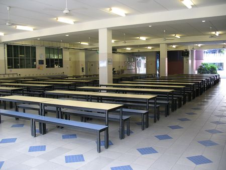 Empty school canteen with lots of chairs and tables.