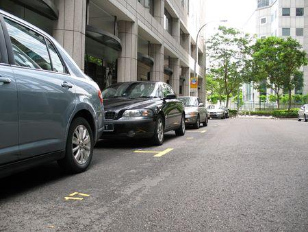 Gli automobili hanno parcheggiato lungo il lato delle strade con copyspace Archivio Fotografico