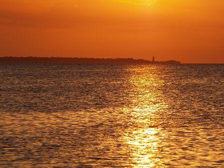 Sea sunset and lighthouse at horizon. photo