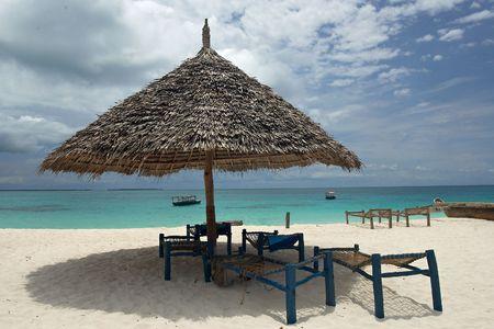 zanzibar: Bekijk de lege dek-stoelen en parasol op het strand. Boten zijn horizon. Indische Oceaan, Zanzibar, Tanzania Stockfoto