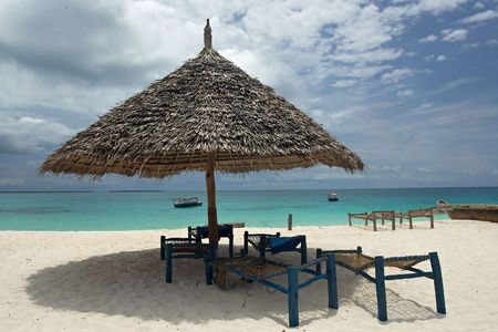 tripping: View of empty deck-chairs and umbrella on the beach. Boats are at horizon. Indian Ocean, Zanzibar, Tanzania