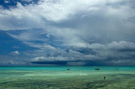 oceanfront: Lonely men and sailboats near oceanfront. Indian Ocean. Island Zanzibar, Tanzania.