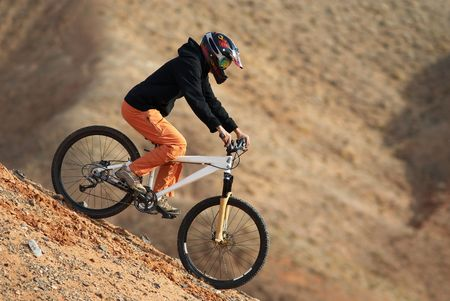 Girl downhill on mountain bike in red canyon Stock Photo - 692325