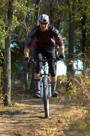 dirt road recreation: Biker in black on forest path Stock Photo