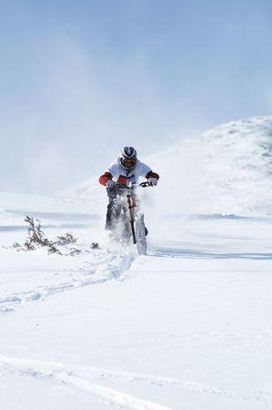 Snow biker downhill on ski resort photo