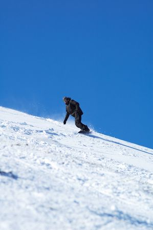 skischool: Black snowboarder and blue sky Stock Photo