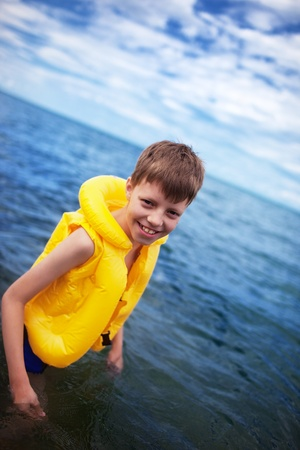 Smiling boy in the life-vest in the water photo