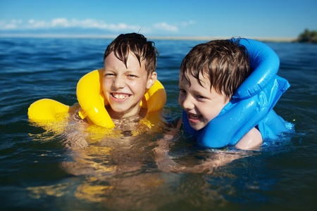 yellow jacket: Smiling brothers swimming in the life jacket
