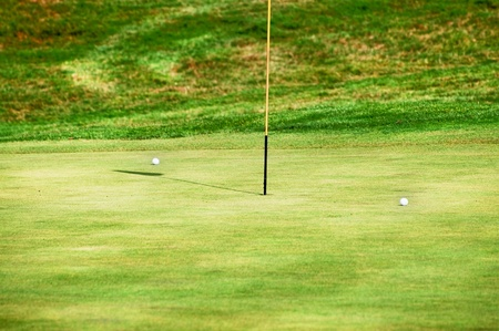 golfball: The green field, a flag and two golf balls Stock Photo