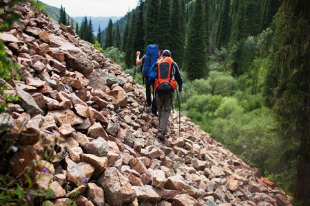 man carrying: Two backpackers in wilderness mountains