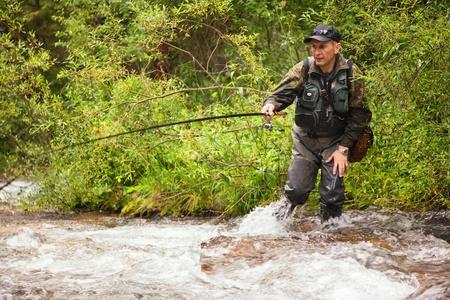 botas altas: La pesca con mosca en el arroyo en el bosque de montaña Foto de archivo