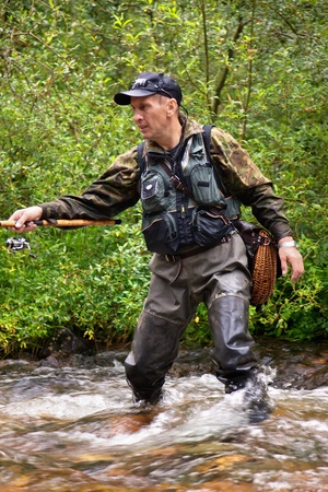 casting: Fly fishing on the creek in mountain forest Stock Photo