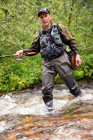 anglers: Fly fishing on the creek in mountain forest Stock Photo