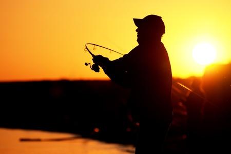 horgász: Fisherman sziluett naplementekor